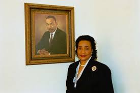 Coretta Scott King standing with a portrait of her late husband, minister, and activist Martin Luther King, Jr. -Source: Wikimedia Commons